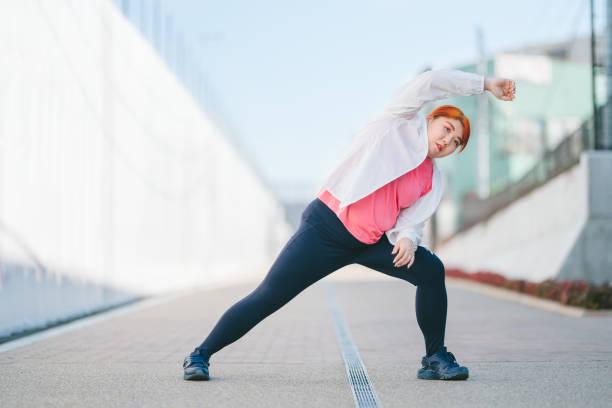 junge frau wärmt sich für sporttraining auf - damen leggings übergrößen stock-fotos und bilder