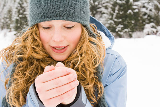 young woman warming up her hands. stock photo