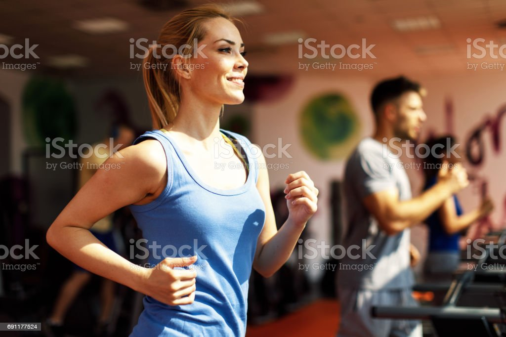 Young woman warming up on treadmill at gym stock photo