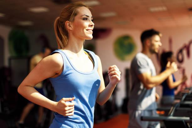 Junge Frau Aufwärmen auf dem Laufband im Fitnessstudio – Foto