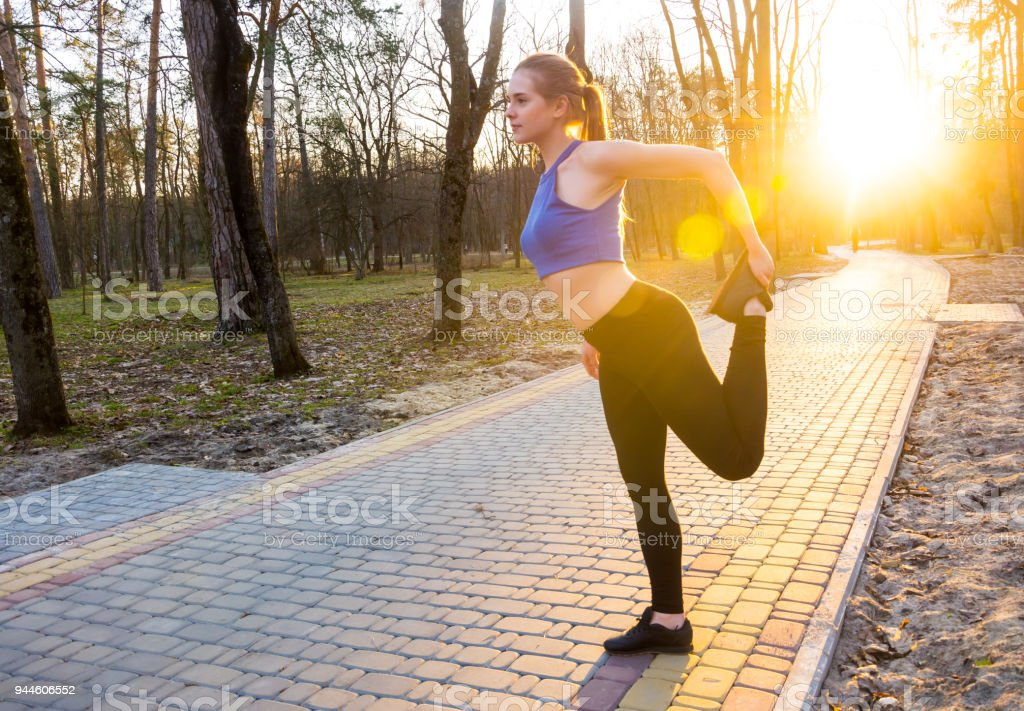 Young woman warms up before running in the park at sunset stock photo