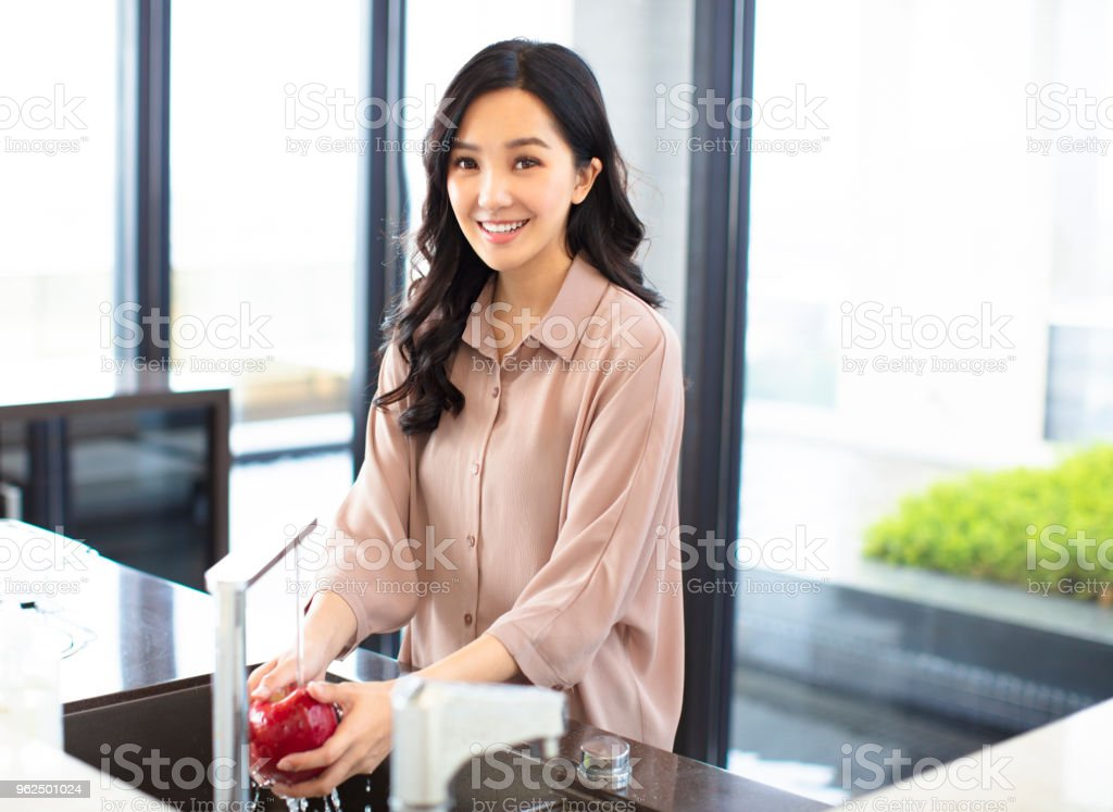young woman wash the fruits in kitchen - Royalty-free Adult Stock Photo