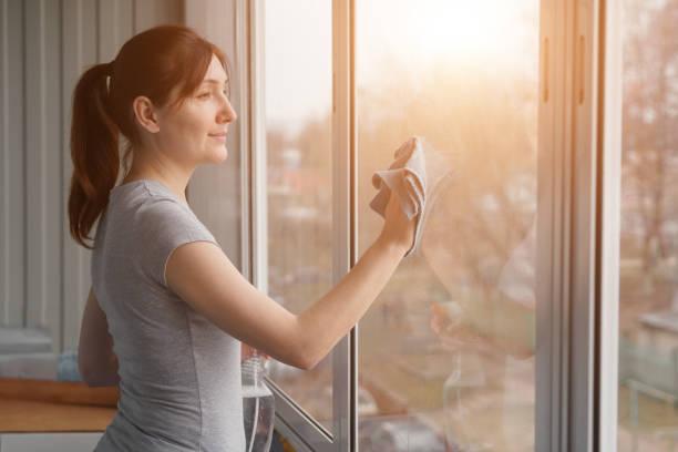 Junge Frau wäscht Windows mit ein blaues Tuch – Foto
