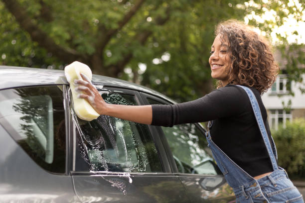 Young woman washing car on driveway stock photo