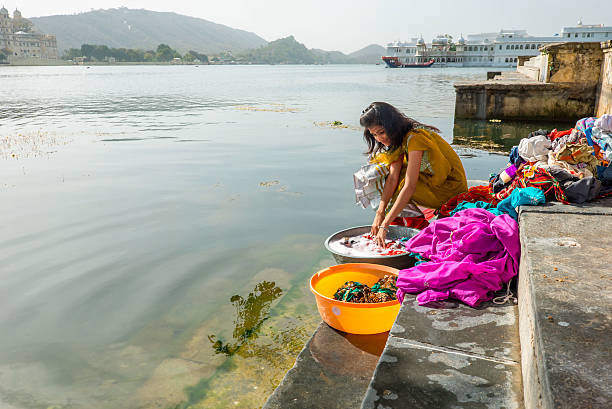 Young woman washing clothes at Ghats, Lake Pichola, Udaipur Woman washing clothes at Ambrai Ghats, Udaipur on Lake Pichola. lake pichola stock pictures, royalty-free photos & images