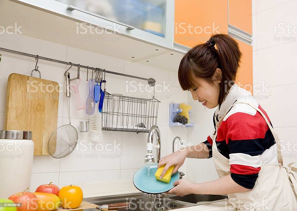 Young woman washing dishes in kitchen sink royaltyfri bildbanksbilder