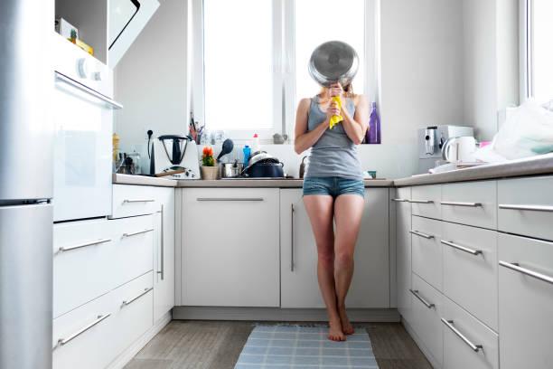 junge frau beim abwasch in der küche - backofenfenster reinigen stock-fotos und bilder
