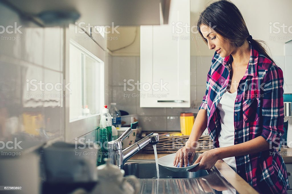 Young woman washing dishes stock photo