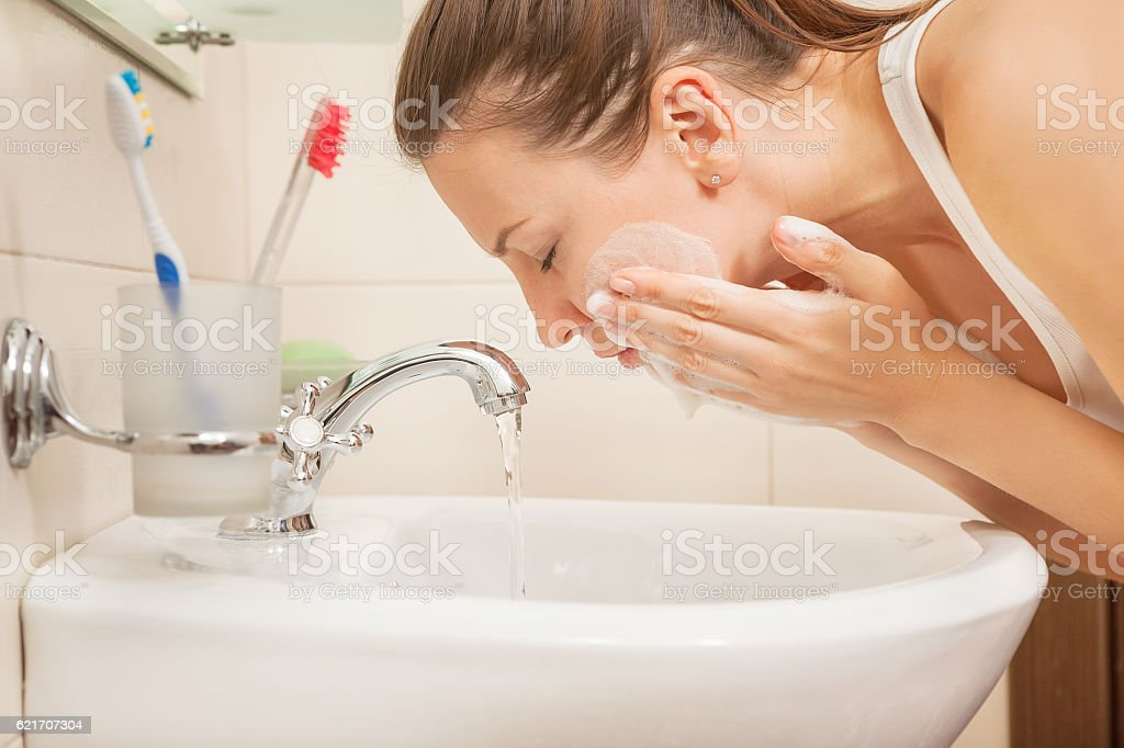 young woman washing face stock photo