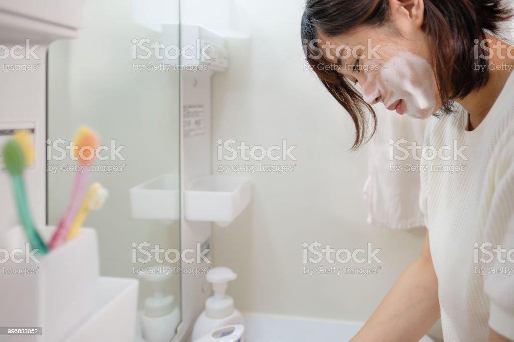 若い女性の顔を洗う ストックフォト