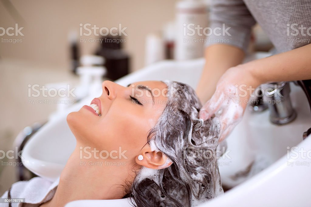 Young woman washing hair in salon stock photo