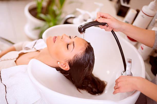 giovane donna di lavaggio dei capelli nel salone di bellezza - lavarsi i capelli foto e immagini stock