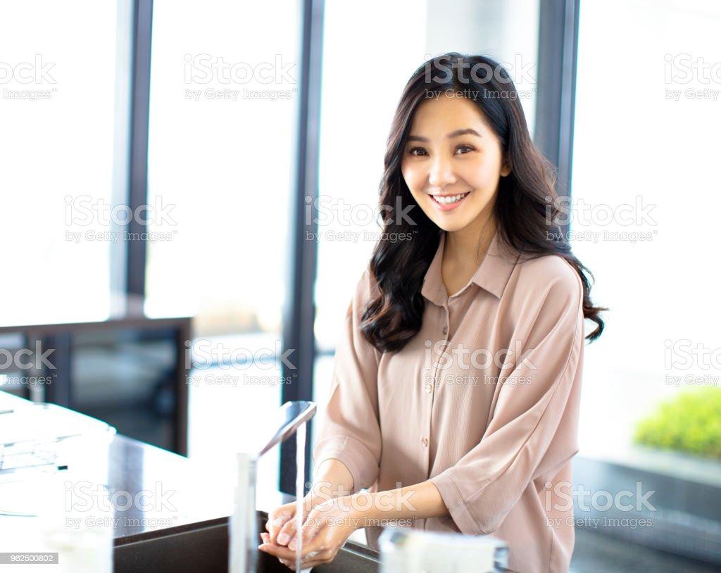 jovem mulher lavando as mãos na cozinha - Foto de stock de Adulto royalty-free