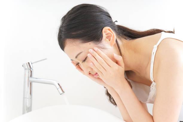 若い女性は彼女の顔を洗う ストックフォト