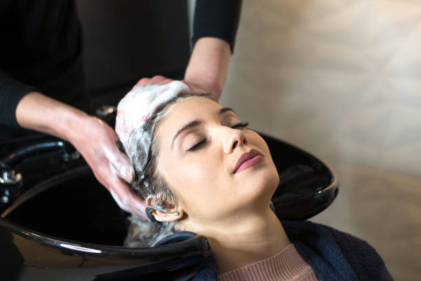 Young woman washing her hair in the hair salon stock photo