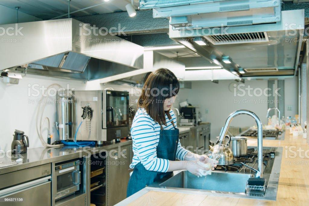 jovem mulher lavar o vidro na cozinha. - foto de acervo