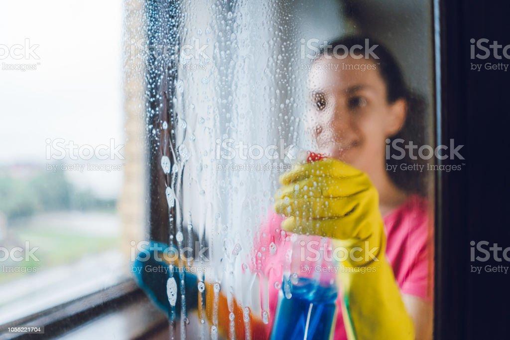 Young woman washing window stock photo