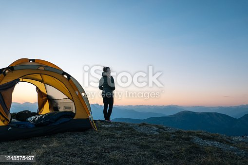 istock Young woman watches sunrise outside camping tent 1248575497
