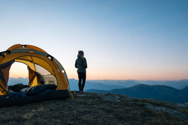 Young woman watches sunrise outside camping tent stock photo