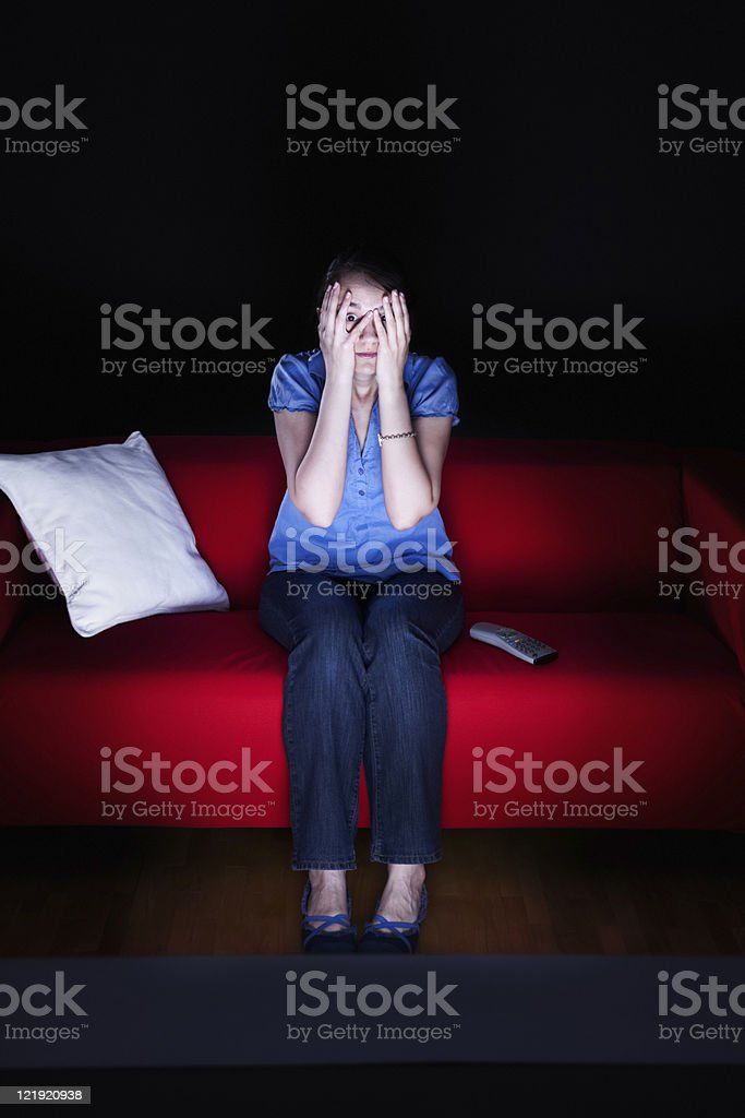 Young woman watching a horror movie royalty-free stock photo