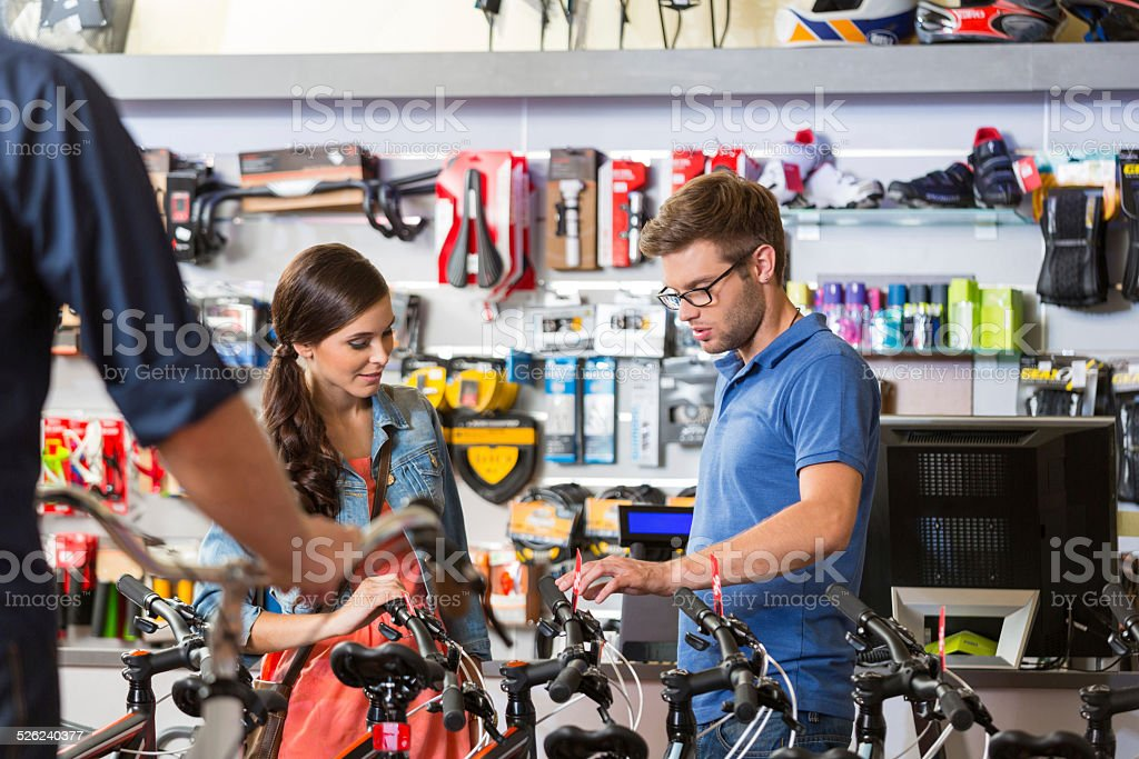 Young woman watching bicycle in sport store Young woman watching a bicycle in bike store, talking with shop assistant. 20-24 Years Stock Photo