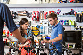Young woman watching a bicycle in bike store, talking with shop assistant.