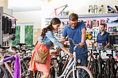 Young woman watching a bicycle in bike store, talking with shop assistant, manager in the background.