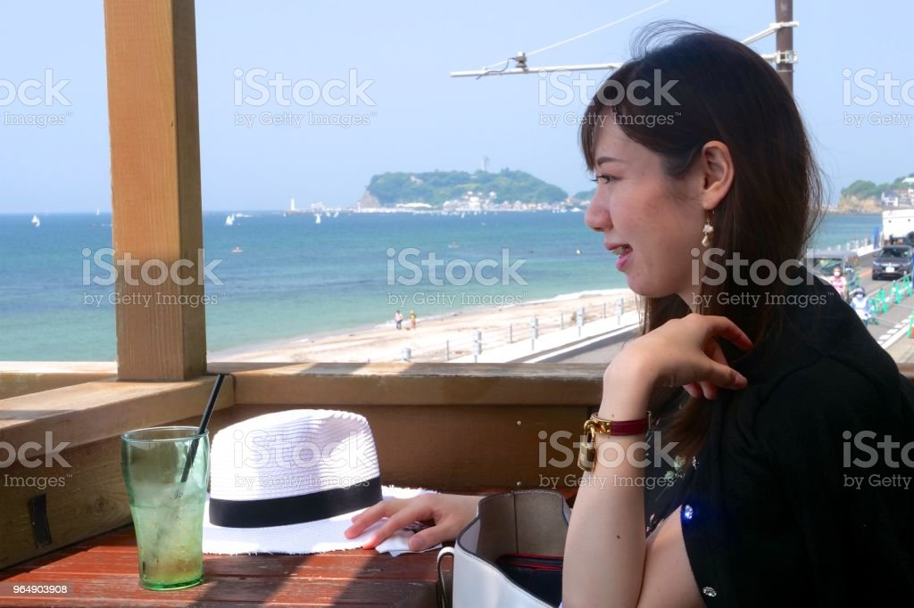 Young woman watching coast at beach side cafe royalty-free stock photo