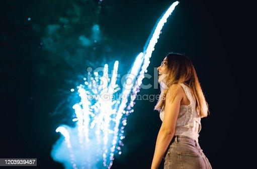 Young woman admiring firework display.
