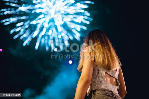 Young woman admiring firework display.