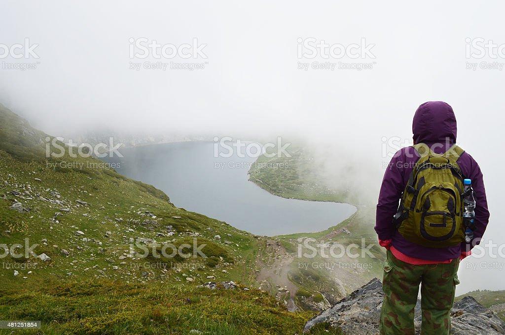 Young woman watching hidden in fog mountain lake stock photo