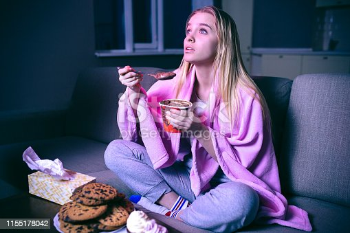 Young woman watching movie at night. Eating ice cream or chocolate with spoon. Cookies on table. Streaming show on tv