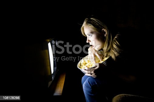 Female sitting infront of the television set eating handfuls of popcorn. She is looking at the television with an amazed look on her face.
