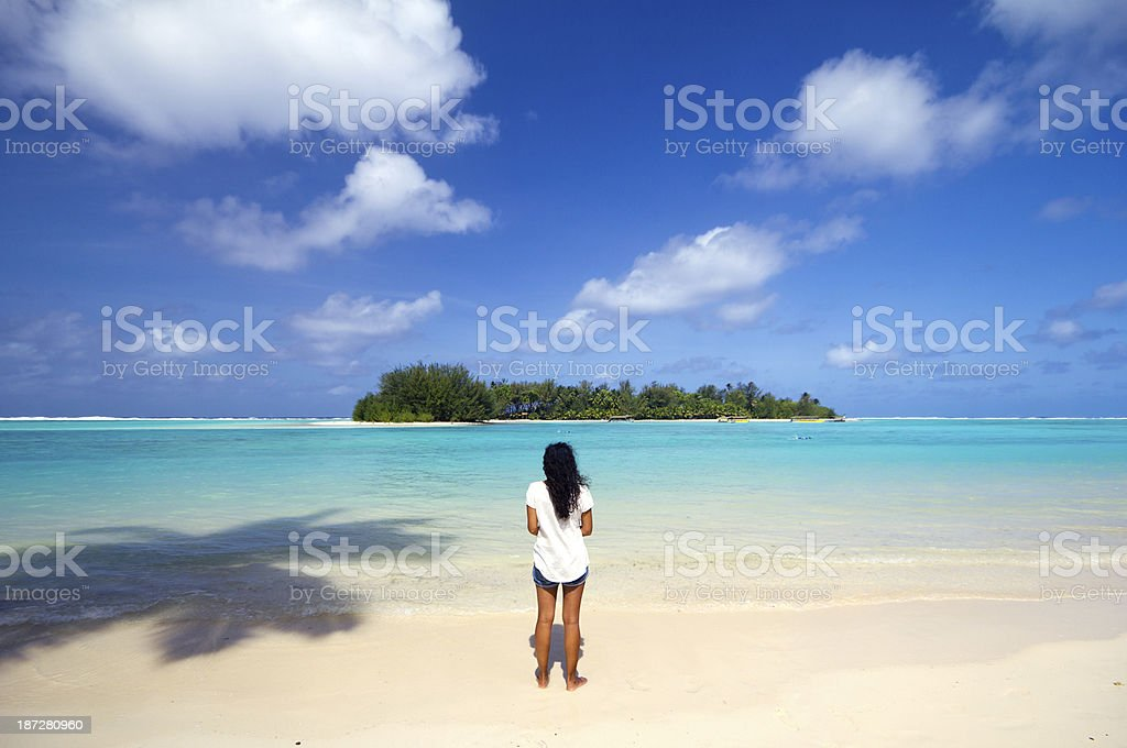 Young woman watching over the turquoise waters of Cook Islands stock photo