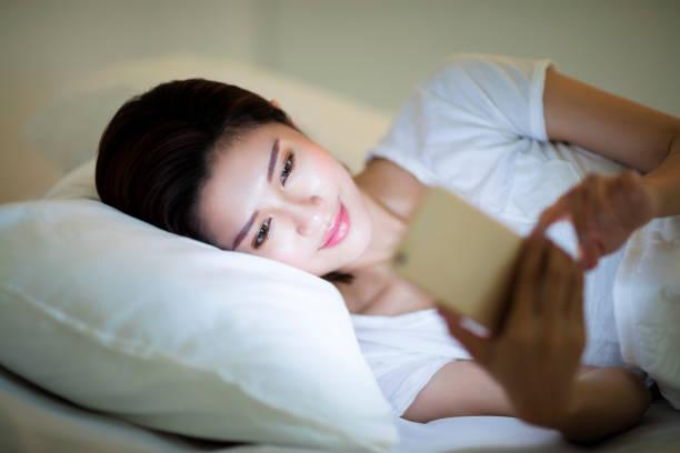 junge frau, die gerade smartphone im bett in der nacht - gute nacht text stock-fotos und bilder