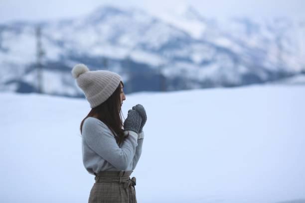 在雪地裡看東西的年輕女子圖像檔