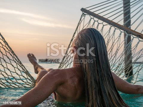 817409212 istock photo Young woman watching sunset from sea hammock 1247659879