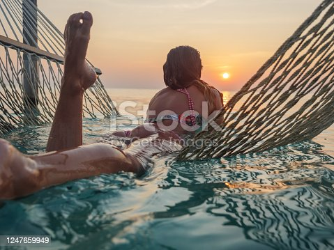 817409212 istock photo Young woman watching sunset from sea hammock 1247659949