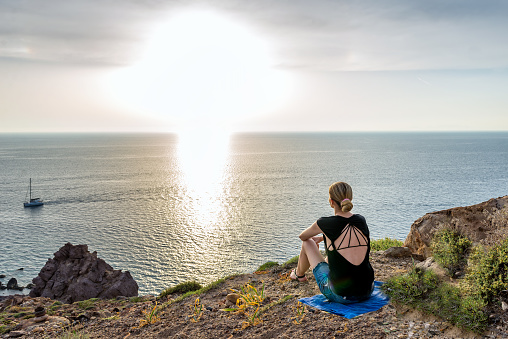 Horizontal color image of young woman sitting on cliff and watching romantic sunset.