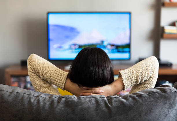 young woman watching television young woman watching television watching stock pictures, royalty-free photos & images