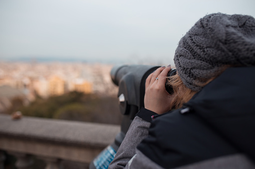 Young woman watching the city through binoculars