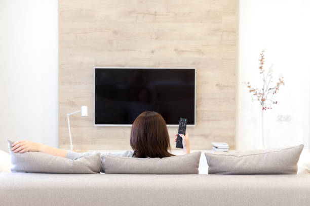 Young woman watching TV in the room stock photo