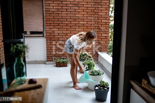 Young woman watering plants on balcony