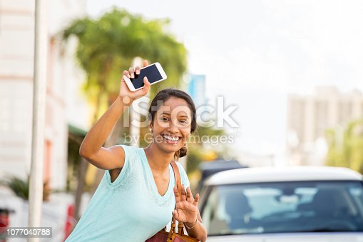 Young woman holding her phone waving her hand for her ride