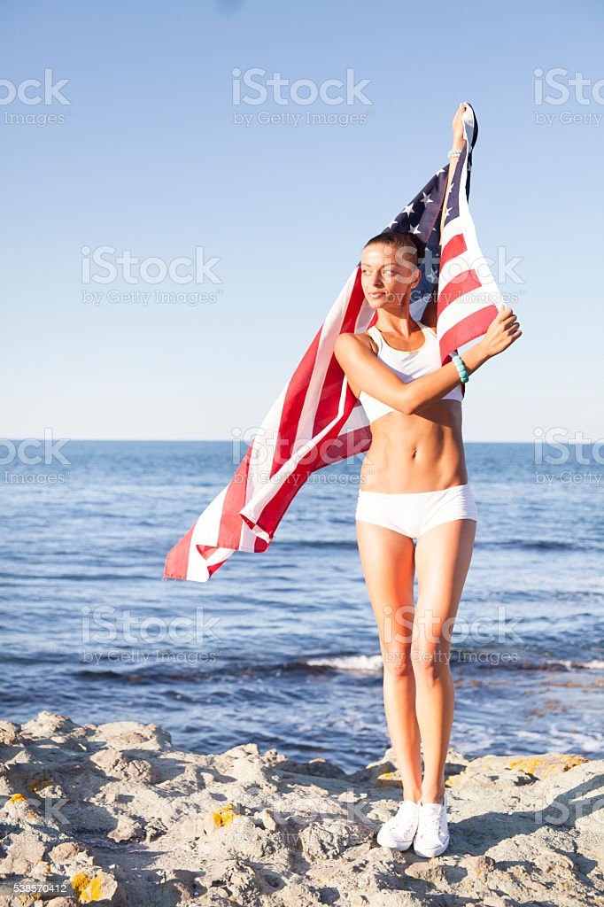 Young woman waving the USA flag at beach stock photo