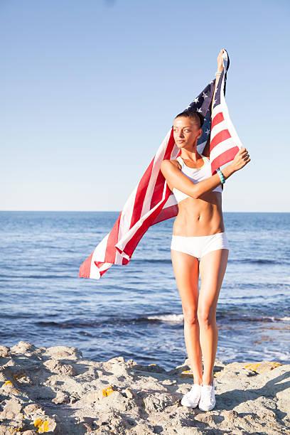 Young woman waving the USA flag at beach stock photo