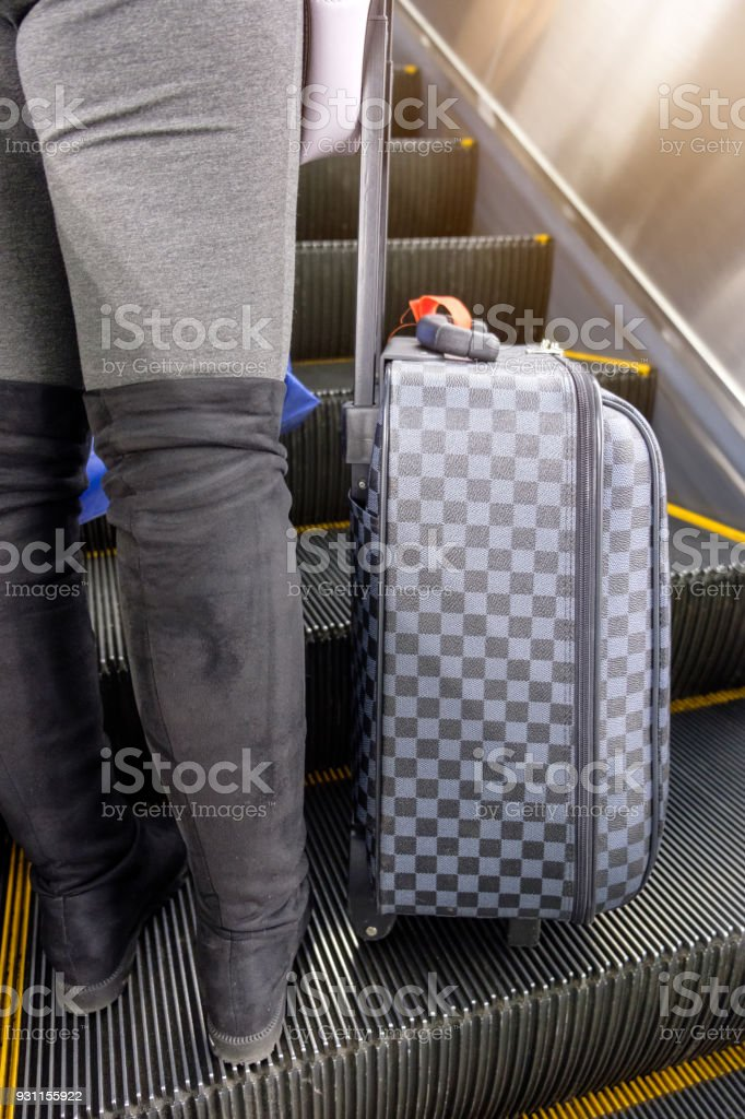 Young woman wear boot lower half with chess luggage standing on escalator stock photo