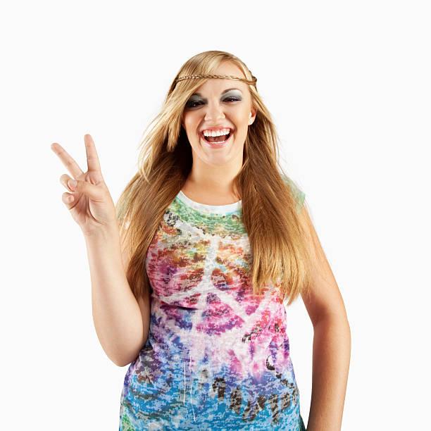 junge frau mit 60er jahre hippie-outfit, mit dem peace-zeichen - hippie kostüm damen stock-fotos und bilder