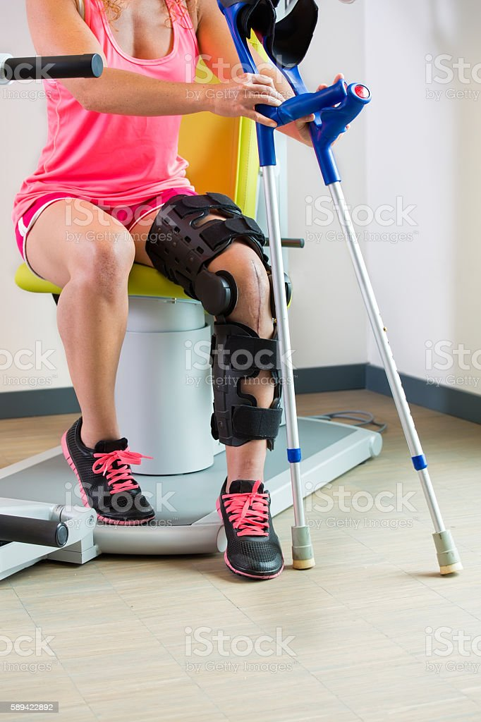 Young woman wearing a brace on her leg. stock photo