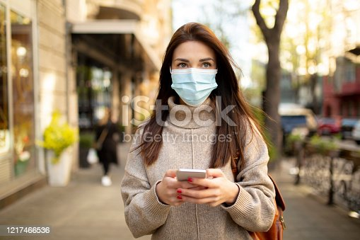 Attractive young woman wearing a face mask and texting on her smart phone while walking trough the city